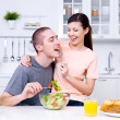 Happy flirting couple in the kitchen -  