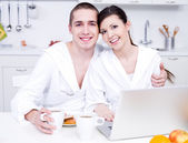 Beautiful smiling lovers in the kitchen — Stock Photo