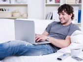 Guy typing on the laptop at home — Stock Photo