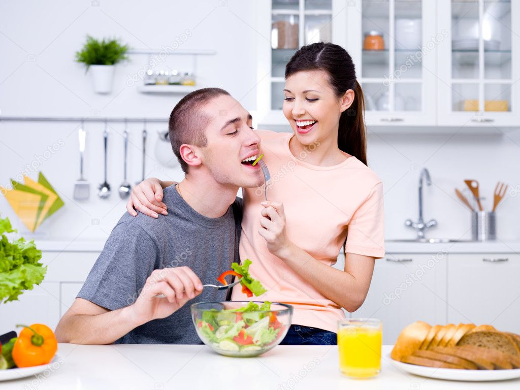 Happy playful young couple eating together in the kitchen — Stock Photo #3159496