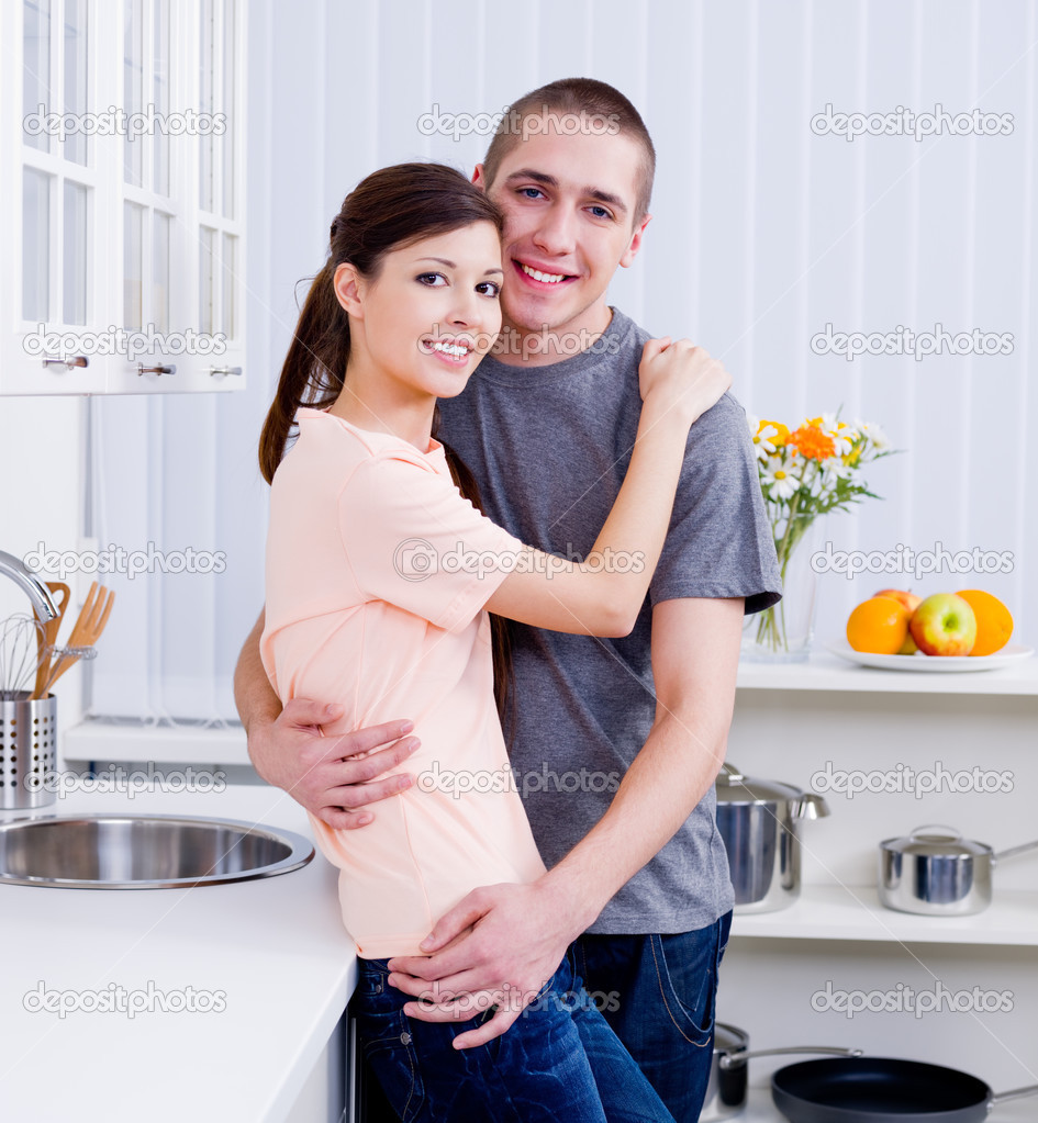 Embracing young loving couple staying together in the kitchen  Stock Photo #3159520