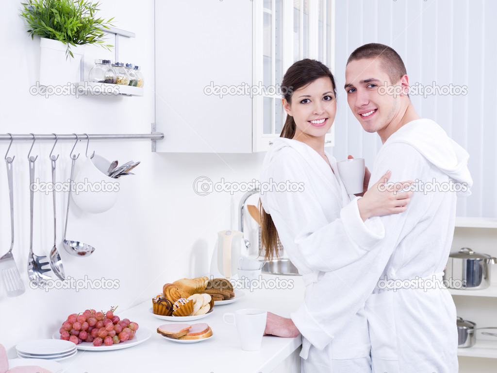Young beautiful smiling couple embracing in the kitchen — Stock Photo #3159535