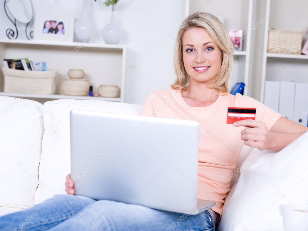 Beautiful smiling young woman with laptop holding credit card  — Stock Photo #3159621