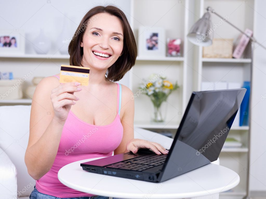 Portrait of happy young beautiful woman holding credit card and using laptop — Stock Photo #3159720