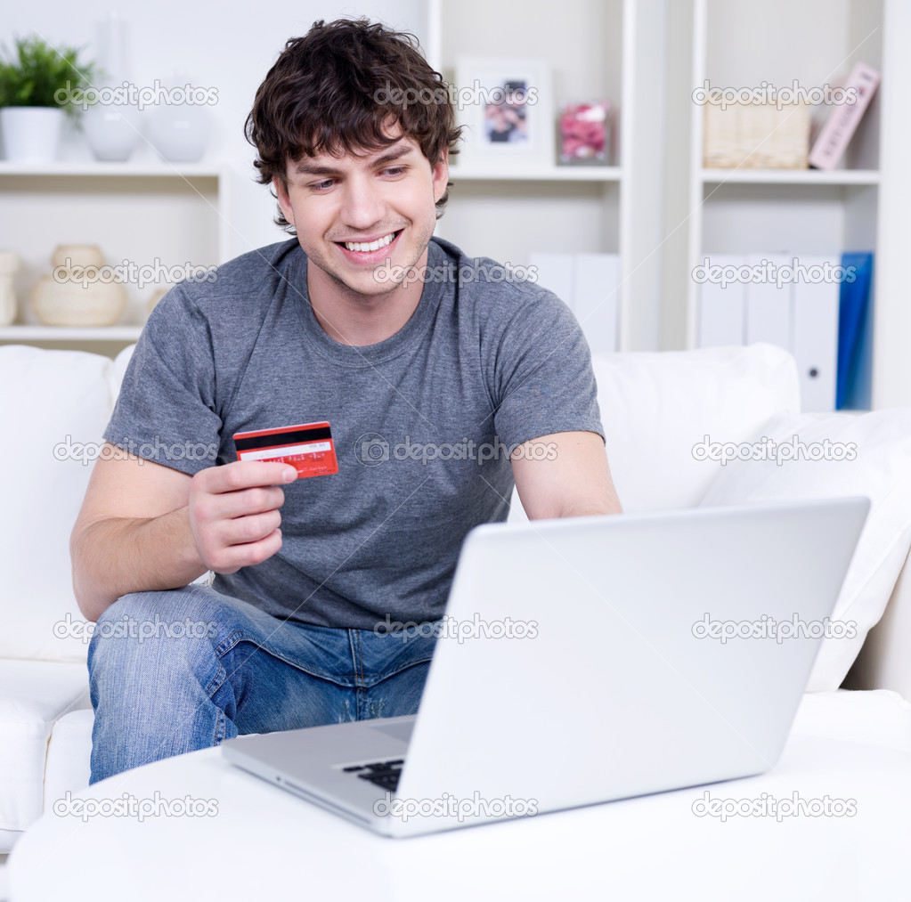Handsome man holding credit card and using laptop for online shopping - indoors — Stock Photo #3159880