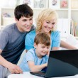 Happy family using laptop at home — Stock Photo
