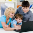 Happy family looking in laptop together — Stock Photo