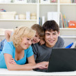 Laptop for happy family at home - Stock Photo