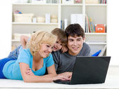 Laptop for happy family at home — Stock Photo