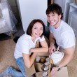 Couple unpacking their things after moving - Stock Photo