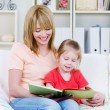 Mother with daughter reading the book — Stockfoto #3468870