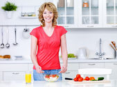 Woman with healthy food in the kitchen — Stock Photo