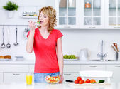 Housewife eating salad in the kitchen — Stock Photo