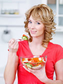 Woman eating heathy salad in the kitchen — Stock Photo