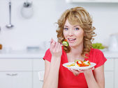 Young woman eating salad in the kitchen — Stok fotoğraf