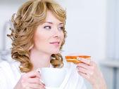 Vrouw met koffie en een sandwich — Stockfoto
