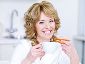 Woman with cup of coffee having breakfast — Stock Photo