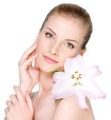 Woman with flower on a shoulder stroking her face — Stock Photo
