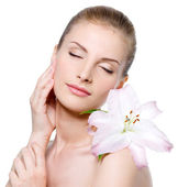 Woman with closed eyes and with lily stroking her face — Stock Photo