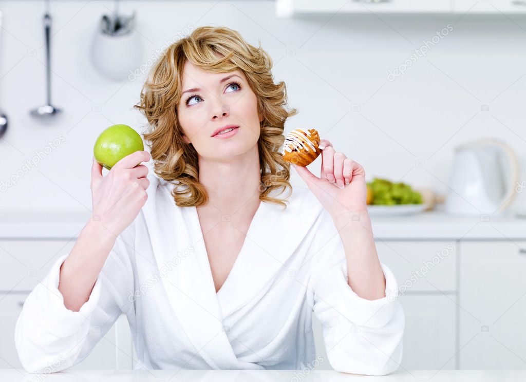 Thinking beautiful woman choosing between healthy food and caloric food - indoors  Stock Photo #3468756