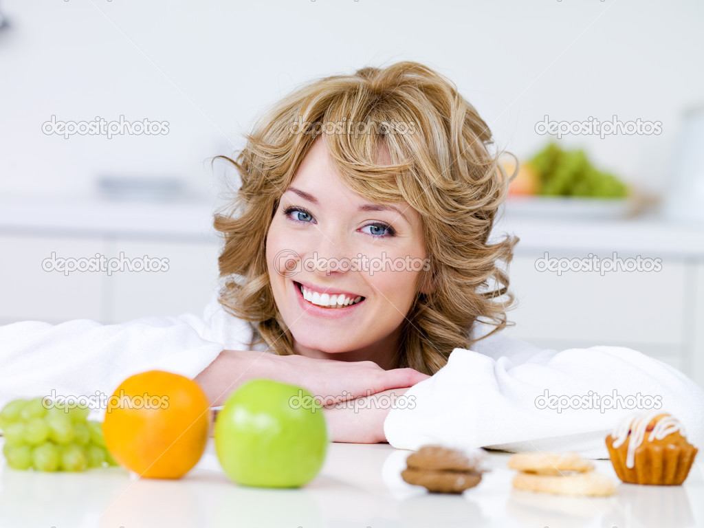 Portrait of beautiful blond woman with fruits and cakes sitting on the kitchen — Stock Photo #3468770
