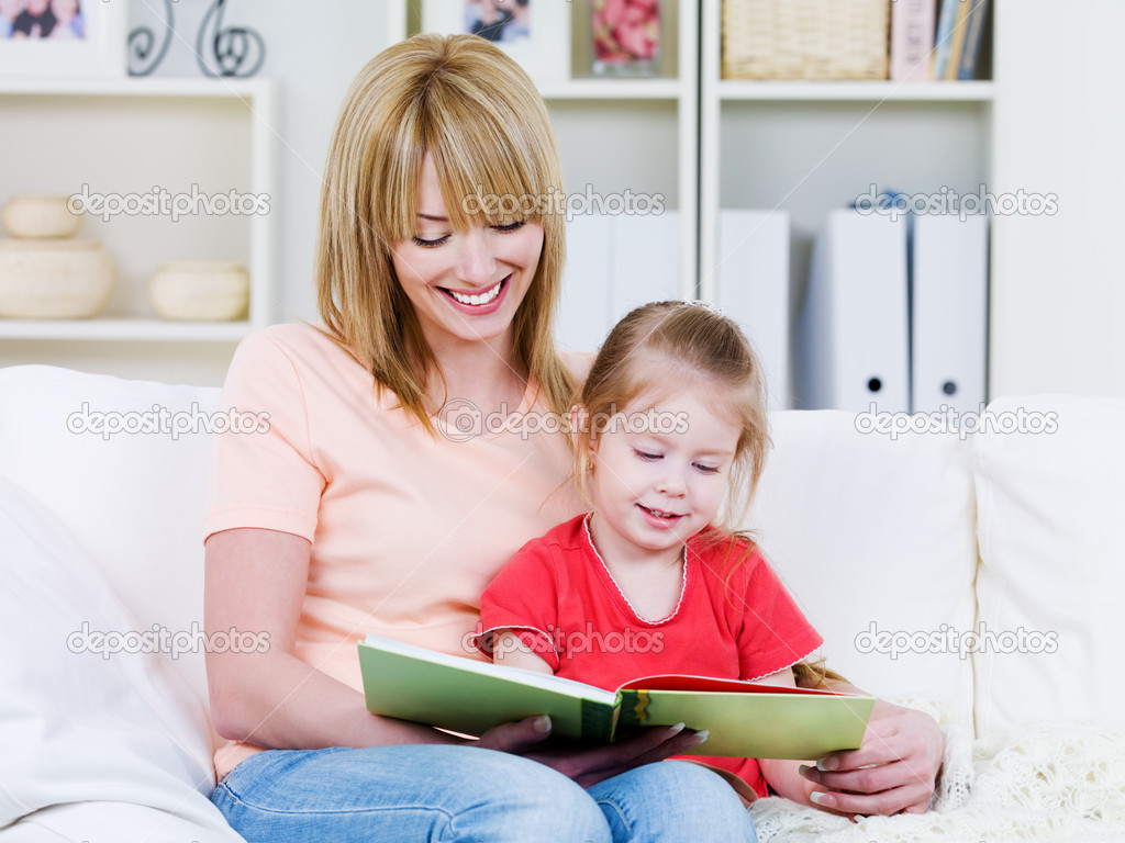 Happy young mother with her little smiling daughter reading the bood together - indoors — Stock Photo #3468870