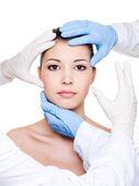 Plastic surgeons touching female face — Stock Photo