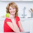 Woman with green apple in the kitchen — Stock Photo #3664374