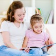 Mother with daughter reading the book — Foto Stock
