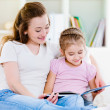 Mother with daughter reading the book — Stockfoto