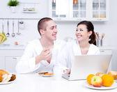 Coppia di innamorati con il portatile in cucina — Foto Stock