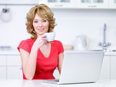Woman with laptop drinking coffee — Stock Photo