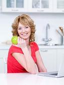 žena s zelené jablko v kuchyni — Stock fotografie