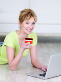 Woman holding credit card and using laptop — Stock Photo