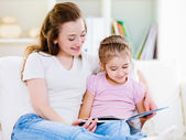 Mother with daughter reading the book — Stock Photo
