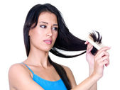 Woman combing ends of her hair — Stock Photo