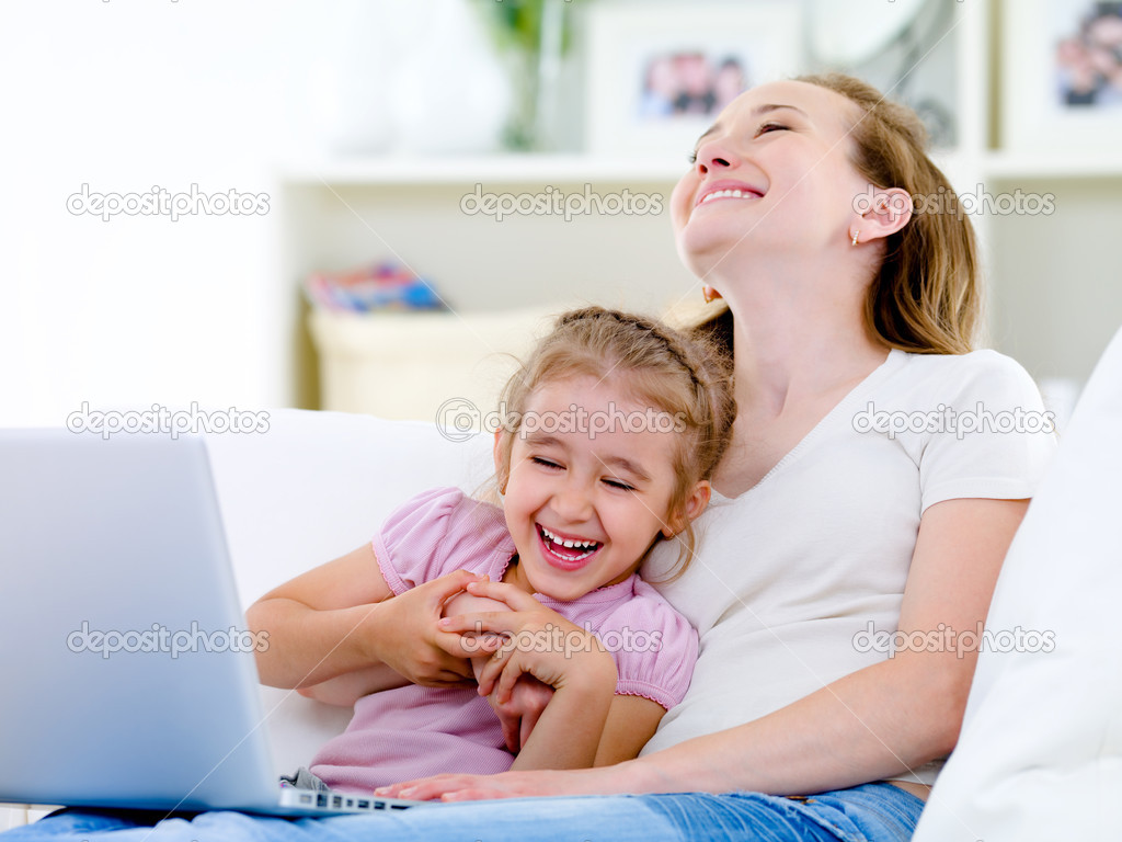 Laughing happy young mother and little daughter with laptop on the sofa at home — Stock Photo #3664938