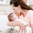 Mother kissing her sleeping baby — Stock Photo