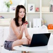 Woman with credit card and laptop at home — ストック写真