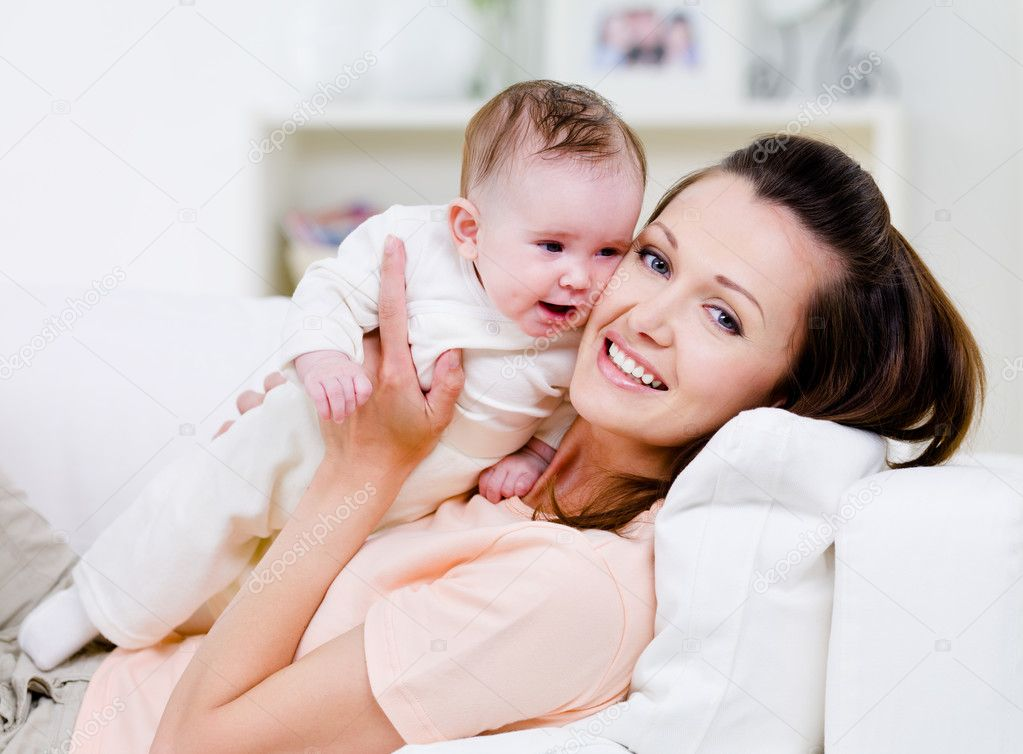 Young smiling happy mother with little baby on the sofa - indoors — Stock Photo #3703677