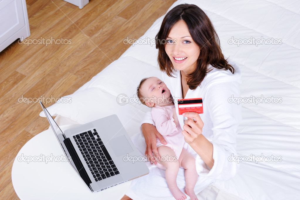 Beautiful young mother sitting with baby and doing internet shopping - high angle  Stock Photo #3703896