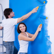 Happy couple painting the wall - Stock Photo