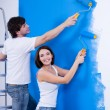 Happy couple painting the wall — Photo