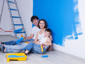 Young family near the painted wall — Stock Photo