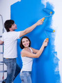 Happy couple painting the wall — Stock Photo