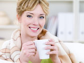 Smiling woman warming with cup — Stock Photo