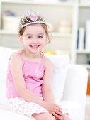 Little happy girl with crown at home — Stock Photo