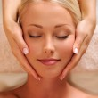 Pretty female face getting relaxation massage of head — Stock Photo #3784468