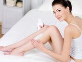 Aplicar a loção para o corpo nas pernas de mulher — Foto Stock