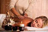 Masseur doing massaging back of a beautiful young woman — Stock Photo